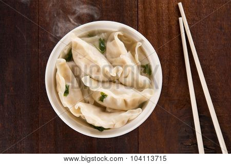 Top view fresh dumplings soup on plate with hot steams. Chinese dish on rustic old vintage wooden background.