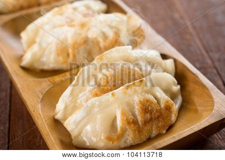 Close up fresh pan fried dumplings on plate with hot steams. Asian dish on rustic vintage wooden background.