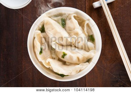 Top view fresh dumplings soup on plate with hot steams. Chinese meal on rustic old vintage wooden background.