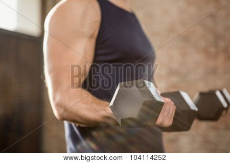 Midsection of man lifting dumbbells at the gym