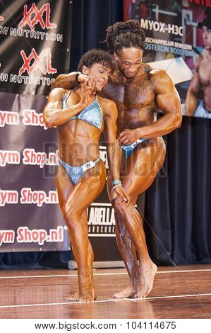 Bodybuilding Duo Embrace Each Other On Stage