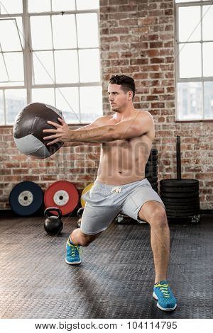 Muscular man exercising with medicine ball at the gym