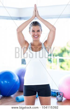 Woman smiling with hands joined overhead in fitness studio