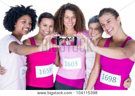 Smiling athletes taking self portrait with smartphone while standing against white background