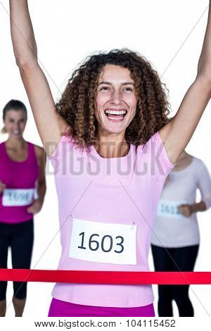 Smiling winner female athlete crossing finish line with arms raised against white background
