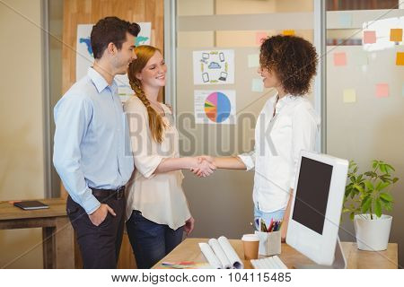 Business woman shaking hand with client in office