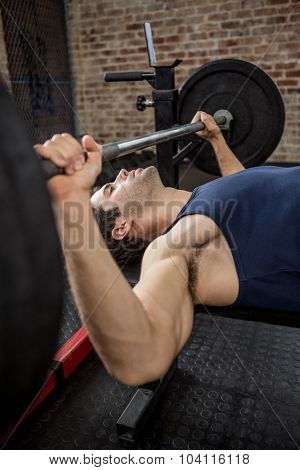 Side view of man holding barbell at the gym