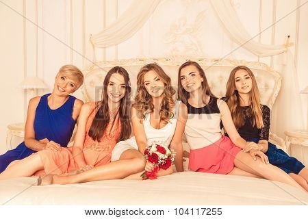 Attractive Cute Girls Celebrate A Bachelorette Party Of Bride Sitting On The Bed