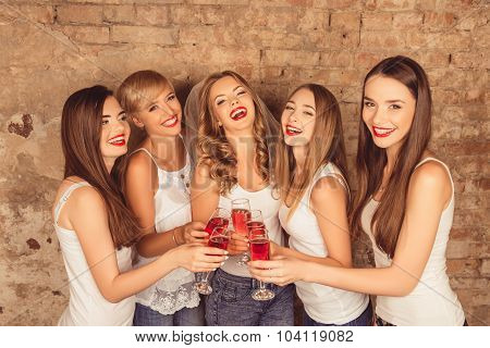 Attractive Bride And Happy Bridesmaids Celebrating Hen-party With Red Champagne