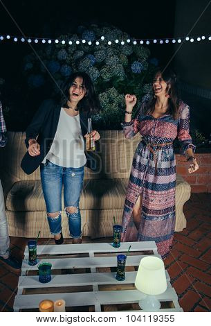 Two women friends dancing and having fun in a party