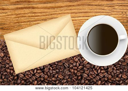 Close-up Of Roasted Coffee Beans And Envelop And Coffee Cup Over Wooden Background