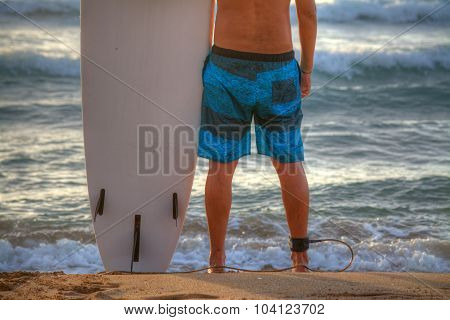 Surfer With Surfboard Standing On The Sand