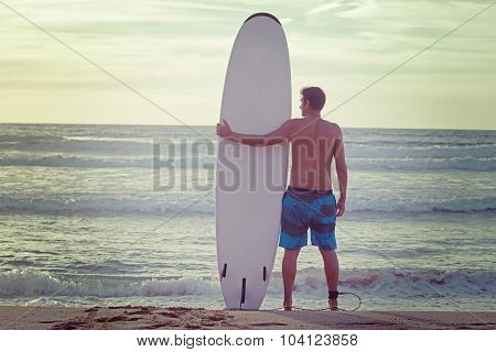 Surfer And Surfboard On The Beach