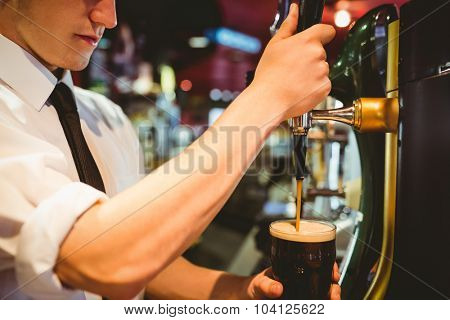 Cropped image of bartender holding beer glass below dispenser tap at bar counter