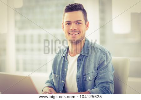 Portrait of smiling young man with laptop while sitting at desk