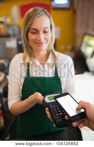 Female worker accepting payment from customer through NFC in bakery