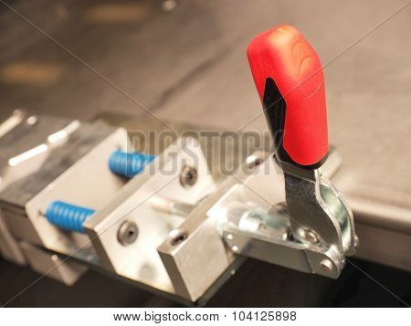 Red plastic lever of an industrial mechanical clamping device