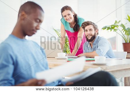 Portrait of business people at desk with person sitting on foreground in office
