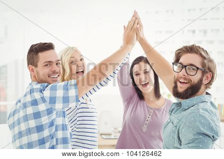 Portrait of smiling business people giving high five at office