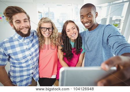 Smiling business people making face for selfie while sitting on desk in office
