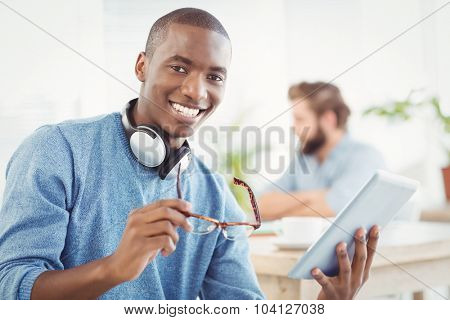 Portrait of smiling man with headphones while holding digital tablet and eyeglasses in office