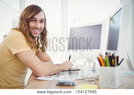 Portrait of happy hipster working at desk in office