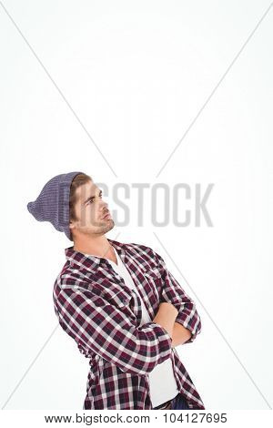 Man with arms crossed looking up standing against white background