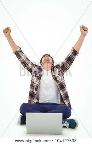 Hipster cheering while working on laptop against white background
