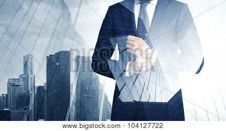 Double exposure of young bearded business man in the skyscraper on background