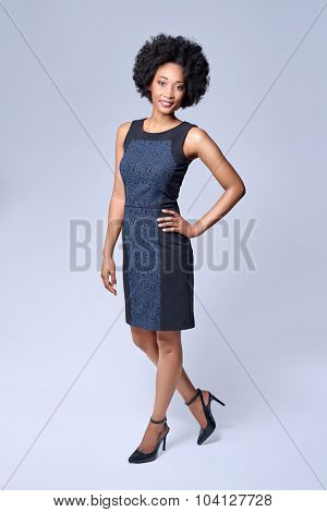 Full length portrait  of attractive young black african model wears smart business dress in studio and smiling