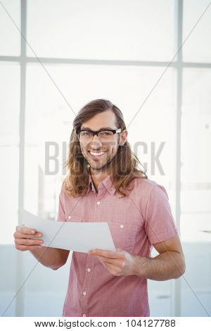 Portrait of happy hipster holding paper against window in office