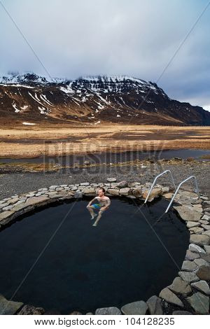 Caucasian travel tourist man soaking in Iceland's natural hot spring on adventure vacation