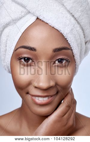 Close up portrait of attractive beautiful black african woman with towel wrapped around her hair, beauty skincare cosmetics concept