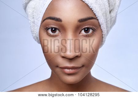 Close up portrait of young beautiful black african woman with towel wrapped around her hair, beauty skincare cosmetics concept