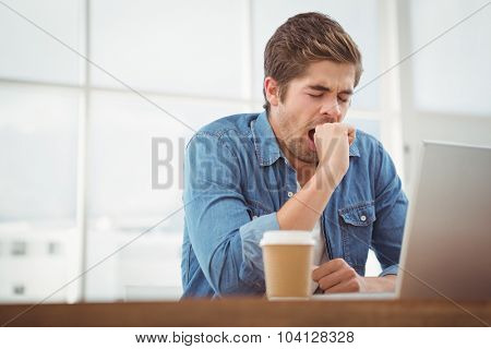 Low angle view of tired businessman sitting at desk in office