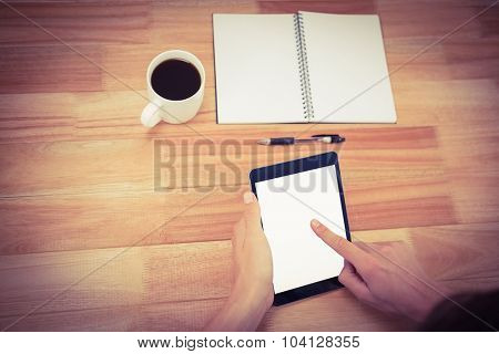 Cropped hand of man using digital tablet with book and coffee on table in office