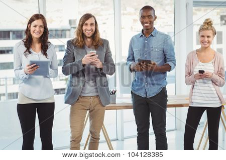 Portrait of cheerful business team using technology while standing at office