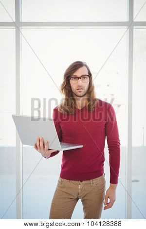 Portrait of creative businessman holding laptop while standing against window in office