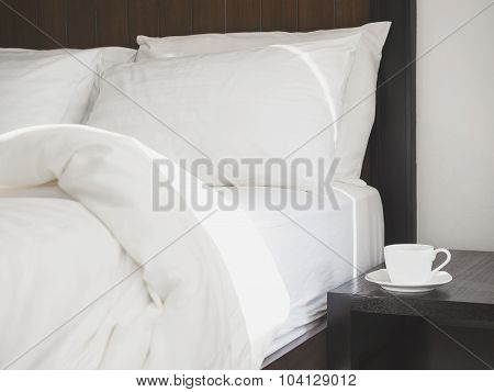 Bed pillows mattress with table and coffee cup