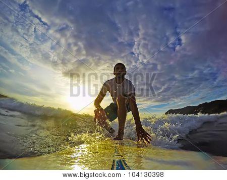 Surfing At Sunset Under Clouds
