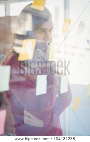 Thoughtful man with hand on chin looking at sticky notes stuck on glass in office