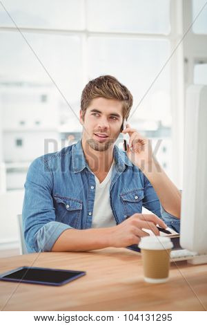 Hipster using mobile phone while sitting at desk in office