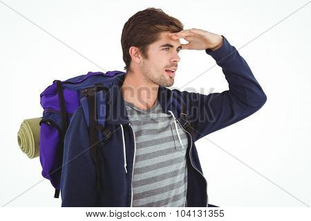 Man with backpack shielding eyes while standing against white background