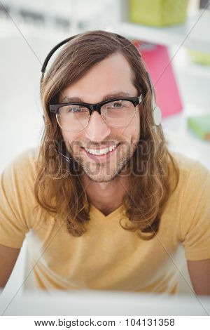 Close-up portrait of happy hipster wearing headphones in office