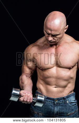 Bald man exercising with dumbbells against black background