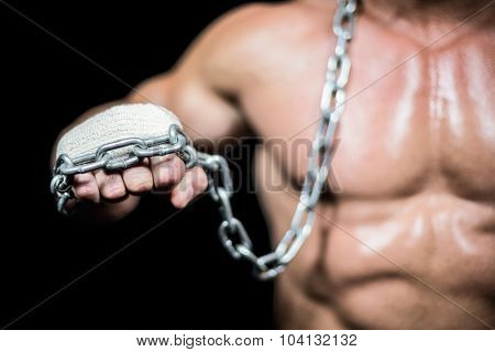 Midsection of bodybuilder fist with chain against black background