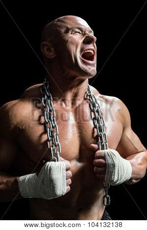Aggressive muscular man holding chain against black background