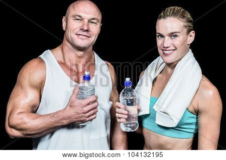 Portrait of confident athlete man and woman with water bottle against black bakground