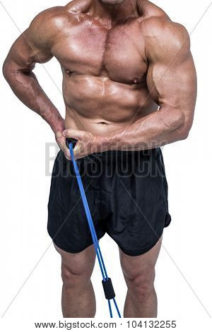 Midsection of bodybuilder pulling elastic rope against white background
