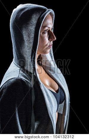 Side view of female athlete in hood against black background